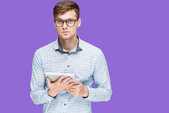 The young man in a shirt working on laptop on lilac backgroundin Royalty Free Stock Photos