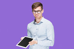 The young man in a shirt working on laptop on lilac backgroundin Royalty Free Stock Photography