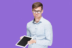 The young man in a shirt working on laptop on lilac backgroundin Royalty Free Stock Image
