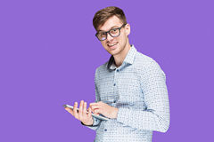 The young man in a shirt working on laptop on lilac backgroundin Royalty Free Stock Images