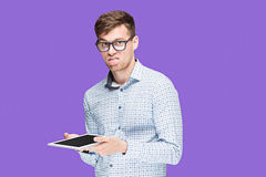 The young man in a shirt working on laptop on lilac backgroundin Stock Photos