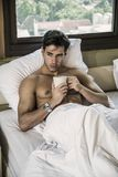 Young man shirtless on his bed with a coffee or tea cup. Handsome young man laying shirtless on his bed next to window, holding a coffee or tea cup stock photo