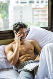 Young man shirtless on his bed with a coffee or tea cup stock photo