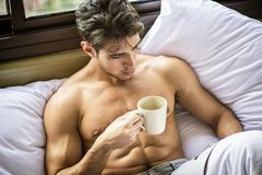 Young man shirtless on his bed with a coffee or tea cup royalty free stock photography