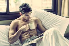 Young man shirtless on his bed with a coffee or tea cup. Handsome young man laying shirtless on his bed next to window, holding a coffee or tea cup while reading royalty free stock photography