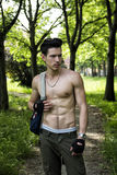 Young man shirtless outdoors hiking with backpack on shoulder Royalty Free Stock Photo