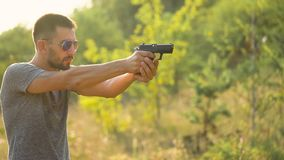 Young man is shooting from a gun, close up. Young man is shooting from a gun, close-up stock footage