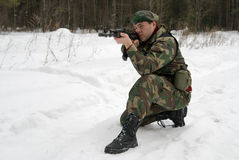 A young man shoots from the automat of kalashnikov. A young man in a camouflage shoots from the automat of kalashnikova stock images