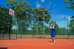 Young man shoots basketball ball Royalty Free Stock Photography