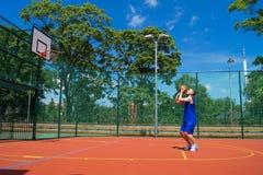 Young man shoots basketball ball Royalty Free Stock Photography