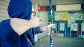 Young man shoots from a sports bow. Young man with glasses in a dark blue sweatshirt with a hood shoots from a bow in the shooting range. Back view. Closeup stock video