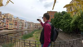 A young man shoots a video with a smartphone near the river Onyar in Girona, Spain stock video footage