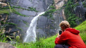 Young man shoots a video of a waterfall in the forest of India stock footage