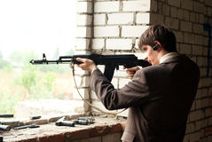 Young man shoots from window Royalty Free Stock Photo