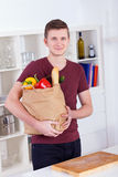 Young man with shopping bag in the kitchen Stock Photography