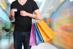 Young man with shopping bags and credit card Royalty Free Stock Photography