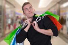 Young man shopping or buying in a mall looking up Royalty Free Stock Photo