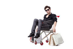 The young man with shopping cart and bags isolated on white Royalty Free Stock Photos