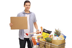 Young man with shopping cart and blank cardboard sign Royalty Free Stock Photography