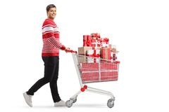 Young man with a shopping cart full of presents walking and smiling at the camera stock photos