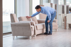 The young man shopping in furniture store Stock Photography