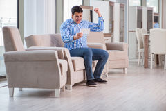 The young man shopping in furniture store Stock Images