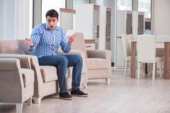 The young man shopping in furniture store Royalty Free Stock Photos