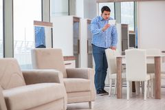 The young man shopping in furniture store Royalty Free Stock Images