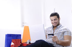 Young man in shopping on-line. Young man buying on internet with laptop in indoor Royalty Free Stock Photography