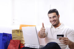 Young man in shopping on-line. Young man buying on internet with laptop in indoor Royalty Free Stock Photos