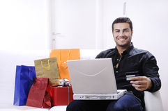 Young man in shopping on-line. Young man buying on internet with laptop in indoor Royalty Free Stock Photo