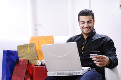 Young man in shopping on-line. Young man buying on internet with laptop in indoor Stock Photography
