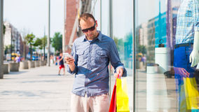 Young man shopping in the mall with many colored shopping bags in his hand. He is holding a phone. Royalty Free Stock Photos