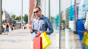 Young man shopping in the mall with many colored shopping bags in his hand. He is holding a phone. Stock Images