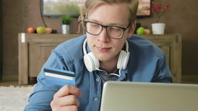 Young man shopping online using credit card and laptop computer stock video