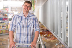 Young man shopping for pre-pack in a grocery store. Young man shopping for frozen food in a grocery store stock photo