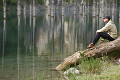 Young man on the shore of a mountain lake Royalty Free Stock Photo