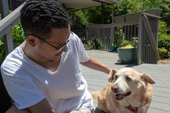 Young man with short dreads on a residential porch petting a dog, sunny day