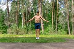 Young man jumping rope in a pine forest stock photo