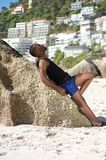 Young man in shorts leaning against rock at the beach Stock Images