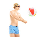 Young man in shorts playing with a beach ball. Isolated on white background Stock Image