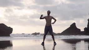 Young man in shorts and sneakers doing stretching exercises on a beach with rocks early in the morning or evening stock footage