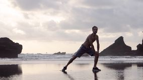 Young man in shorts and sneakers doing stretching exercises on a beach with rocks early in the morning or evening stock video footage
