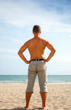 Young man in shorts stands on the sandy beach Royalty Free Stock Image