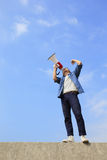 Young man shout megaphone. Young man shout by megaphone with blue sky background, asian Royalty Free Stock Photo