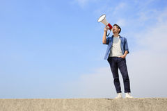 Young man shout megaphone. Young man shout by megaphone with blue sky background, asian Stock Photography
