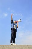 Young man shout megaphone. Young man shout by megaphone with blue sky background, asian Stock Image