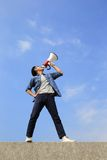 Young man shout megaphone. Young man shout by megaphone with blue sky background, asian Royalty Free Stock Image