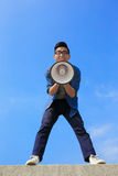 Young man shout megaphone. Young man shout by megaphone with blue sky background, asian Royalty Free Stock Photography