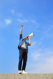 Young man shout megaphone. Young man shout by megaphone with blue sky background, asian Stock Photo